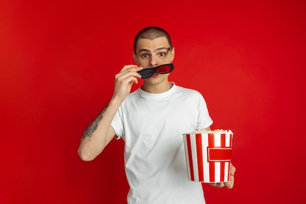 Crazy shocked, numb. caucasian young man's portrait on red  wall. beautiful male model with popcorn.