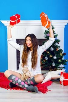 クリスマスを開く狂気の笑顔の女の子を提示します。暖炉と新年装飾の木の近くに座っています。前向きな感情と幸福。