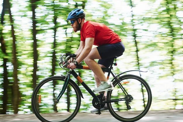 クレイジースピード。自転車のサイクリストは晴れた日に森のアスファルト道路に