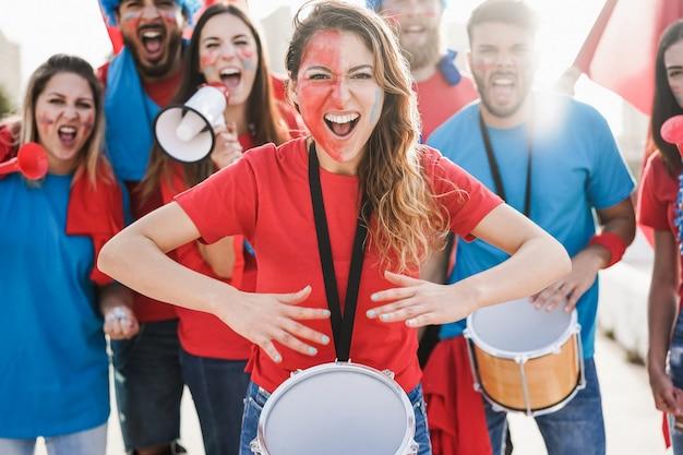 팀을 지원하면서 드럼을 연주하고 비명을 지르는 미친 스포츠 팬-중앙 여성 얼굴에 집중