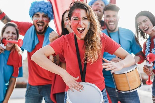 팀을 지원하면서 드럼을 연주하고 비명을 지르는 미친 스포츠 팬-중앙 여성에 집중