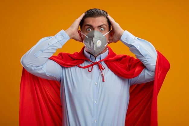 Uomo d'affari pazzo super eroe in maschera facciale protettiva e mantello rosso che guarda l'obbiettivo con sguardo stupito pazzo di sorpresa che tengono le mani sulla sua testa in piedi su sfondo arancione
