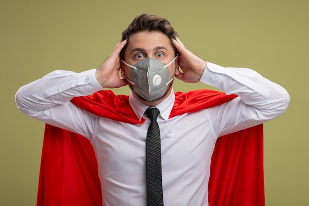 Crazy super hero businessman in protective facial mask and red cape  with crazy amazed look of surprise holding hands on his head standing over green wall