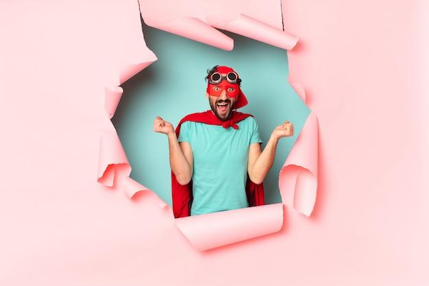紙の穴で勝者のように勝利を祝うクレイジーなスーパーヒーローの男