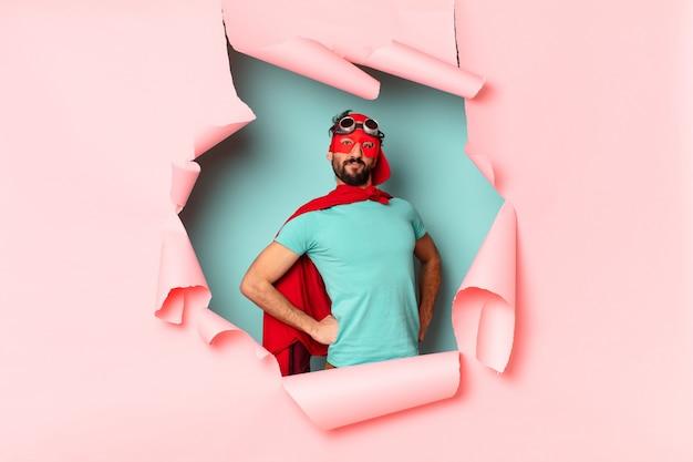 紙の穴で幸せにそして誇りに思っているクレイジーなスーパーヒーローの男