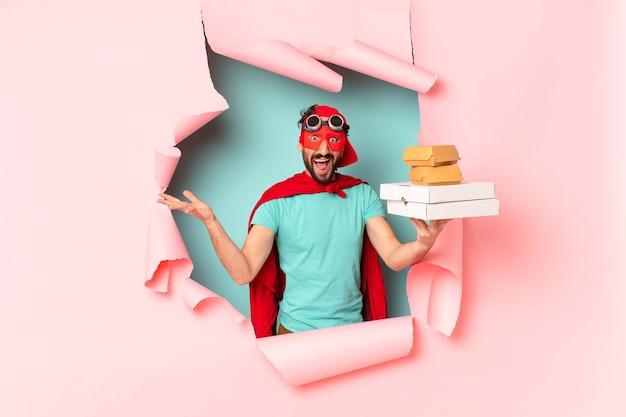 Сумасшедший супергерой человек счастливо и гордо забирает концепцию фаст-фуда