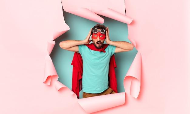 紙の穴にショックを受けた、または驚いた表情のクレイジーなスーパーヒーローの男