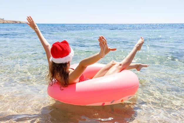 여름 화창한 날에 해변에서 풍선 도넛과 크리스마스 모자로 미친 수영