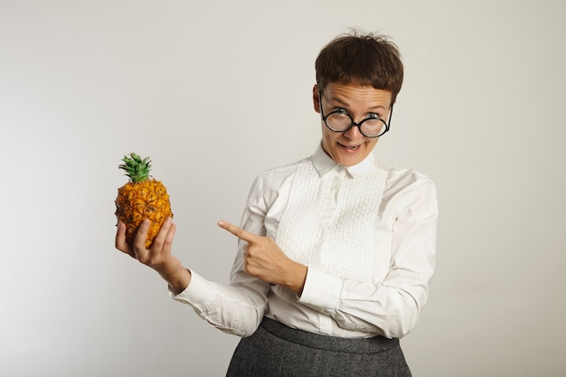 Crazy teacher makes funny face pointing at a pineapple in her hand on white wall