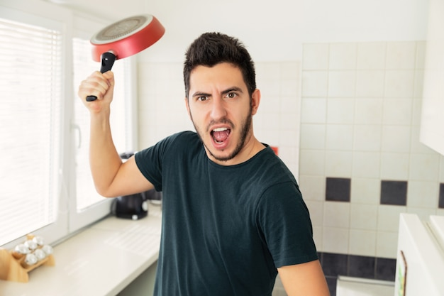 Crazy very angry young man threatening with frying pan on the kitchen.