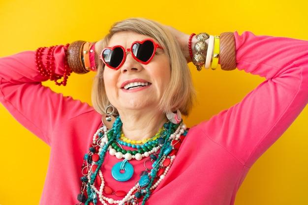 세련된 옷을 입고 즐겁게 노는 미친 여자, 배경색이 있는 노인에 대한 개념
