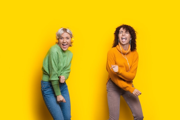 Crazy women with headphones are dancing on a yellow studio wall wearing casual clothes and smiling at camera