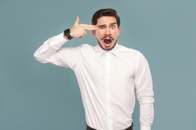 Crazy young businessman with shocked face showing gun sign. suicide concept. portrait of sad bearded businessman in white shirt, with smart watch. indoor studio shot, isolated on light blue background