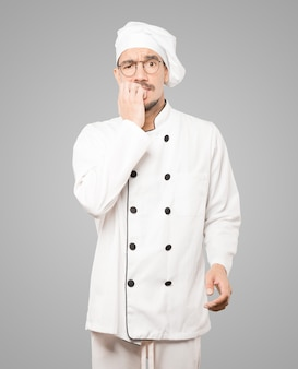 긴장 제스처를 만드는 미친 젊은 요리사