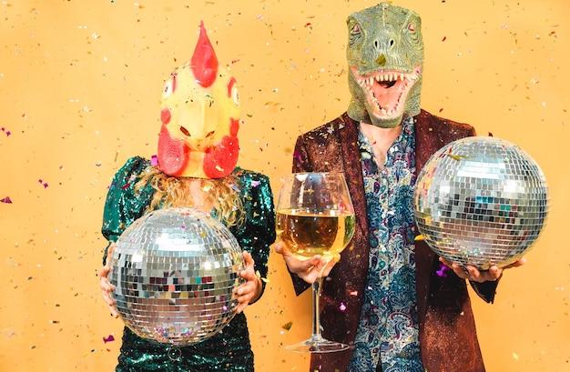 미친 젊은 부부는 t- 렉스와 치킨 마스크를 쓰고 새해 전날 파티에 재미-축제 이벤트에서 축하 패션 사람들-휴일 개념-얼굴에 초점