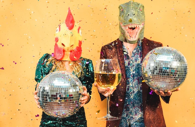 Crazy young couple having fun for new year's eve party wearing t-rex and chicken mask - fashion people celebrating at fest event - holidays concept - focus on faces