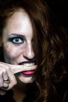 Crazy young girl bites herself on the finger. emotional portrait. on black background.