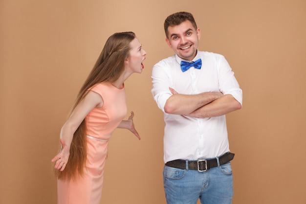 ピンクのドレスを着たクレイジーな若い長い髪のブロンドの女性が立って男に叫んでいます