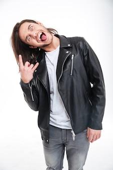 Сумасшедший молодой человек в черной кожаной куртке показывает язык и делает рок-жест на белом фоне