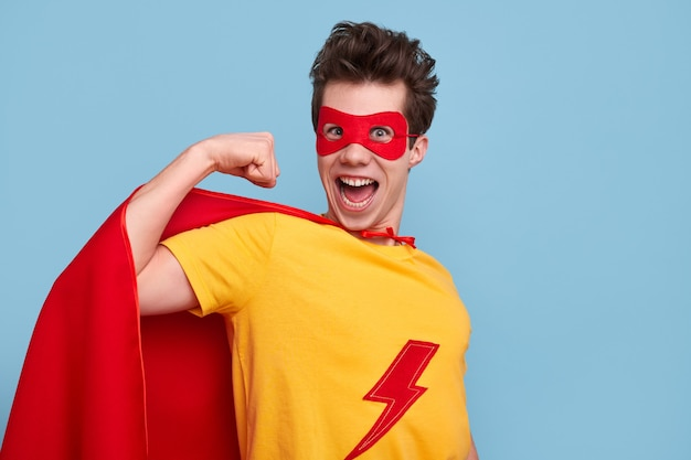 口を開けてカメラを見て、青い背景に上腕二頭筋を示すスーパーヒーローの衣装を着たクレイジーな若い男
