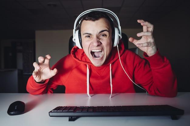 Сумасшедший молодой человек играет в игру дома на вашем компьютере. эмоциональный геймер злится за то, что его убили в компьютерной игре.