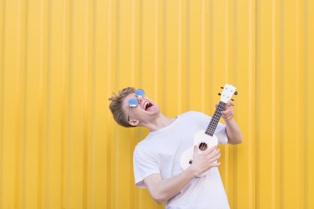 Crazy young man plays ukulele on a yellow wall. expressive musician playing guitar. musical concept