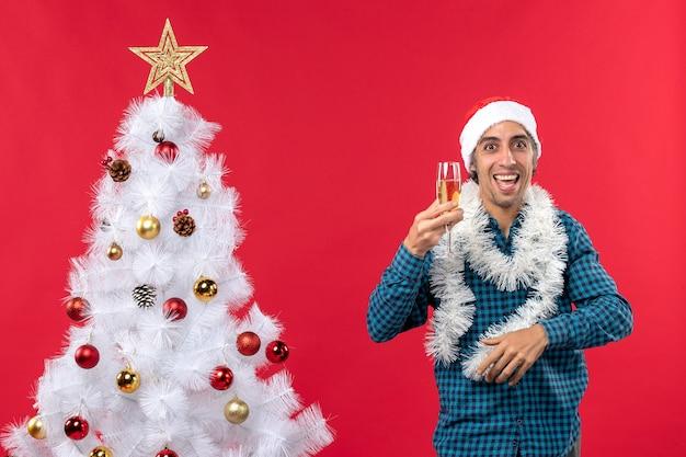 サンタクロースの帽子とワインのグラスを上げるクレイジーな若い男は、クリスマスツリーの近くで自分自身を応援します