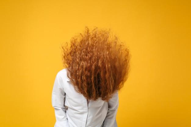 노란색 오렌지 벽에 고립 된 캐주얼 흰색 셔츠 포즈에 미친 젊은 빨간 머리 여자 소녀