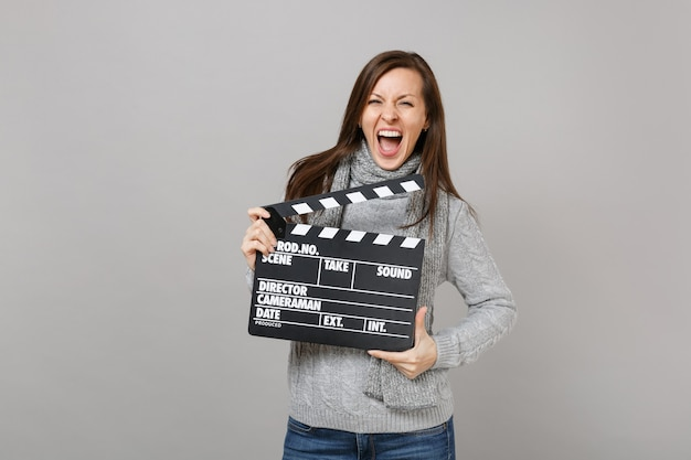 Crazy young woman in gray sweater, scarf screaming, holding classic black film making clapperboard isolated on grey background. healthy fashion lifestyle, people sincere emotions, cold season concept.
