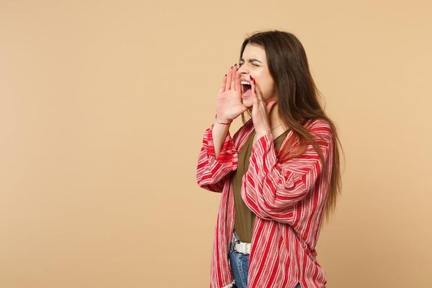 캐주얼 옷을 입은 미친 젊은 여성은 눈을 감고 스튜디오의 파스텔 베이지색 배경에 격리된 입 근처에서 손을 비명을 지르고 있습니다. 사람들은 진심 어린 감정, 라이프 스타일 개념입니다. 복사 공간을 비웃습니다.