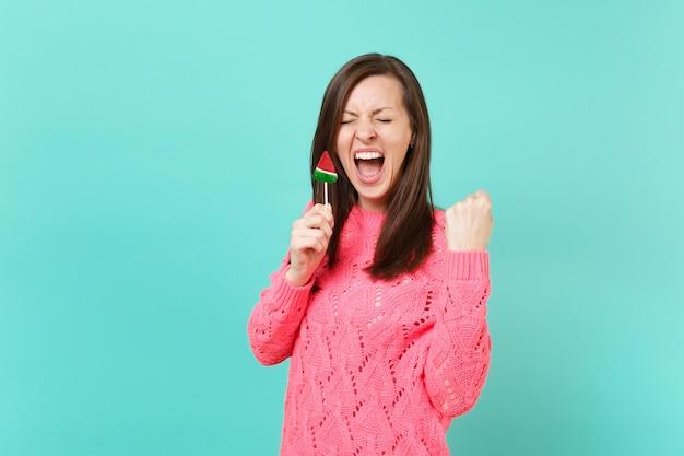 目を閉じて叫んで、勝者のジェスチャーをして、青い背景に分離されたスイカのロリポップを手に持って、ニットのピンクのセーターを着たクレイジーな若い女性。人々のライフスタイルの概念。コピースペースをモックアップします。