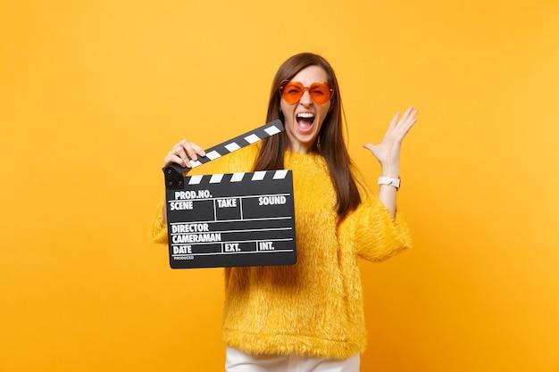 オレンジ色のハートの眼鏡をかけて手を広げて叫んでいるクレイジーな若い女性は、黄色の背景に分離されたカチンコを作る古典的な黒いフィルムを保持します。人々は誠実な感情、ライフスタイル。広告エリア。
