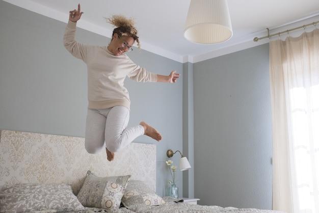 クレイジーな若い女性が自宅のベッドでジャンプします。夢中になっている大喜びの女性。モダンなアパートの寝室での成功を祝う興奮でダンスとベッドの上でジャンプするのんきな女性