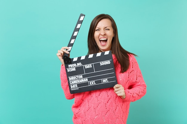 Crazy young woman in knitted pink sweater screaming hold in hand classic black film making clapperboard isolated on blue wall background, studio portrait. people lifestyle concept. mock up copy space.