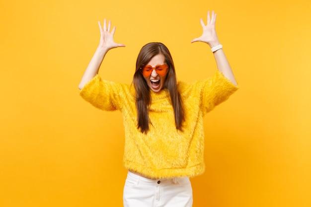 모피 스웨터를 입고 눈을 감고 하트 오렌지색 안경을 낀 미친 젊은 여성, 밝은 노란색 배경에 고립된 손을 위로 들어 올립니다. 사람들은 진심 어린 감정, 라이프 스타일 개념입니다. 광고 영역입니다.