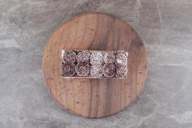 Ломтик торта, покрытый кремом и какао-порошком, на доске на мраморе