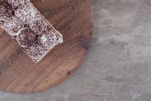 크림과 코코아 가루가 대리석 보드에 케이크 조각을 얹었습니다.