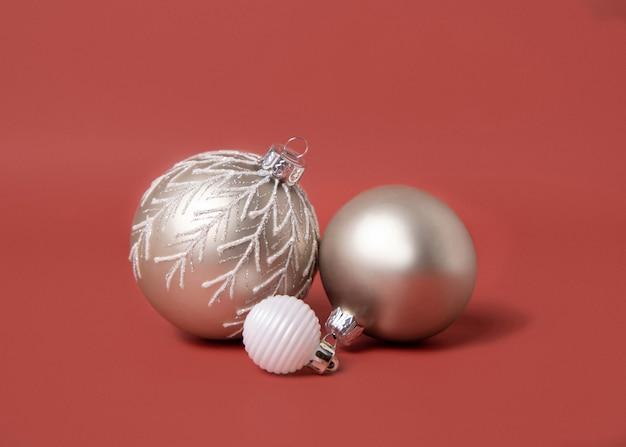 Кремовые и белые рождественские безделушки на красном фоне крупным планом