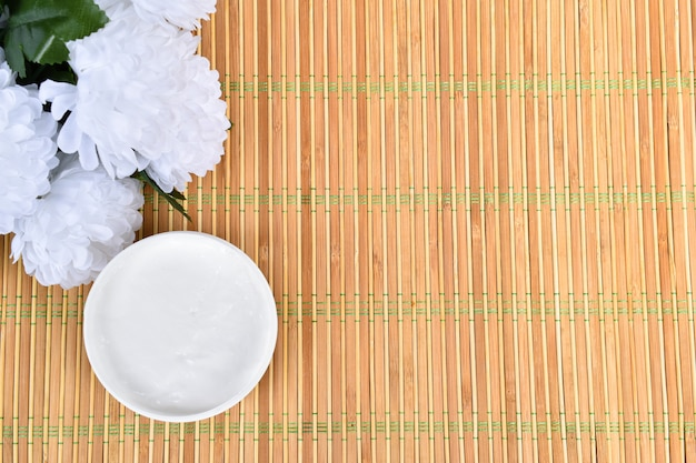 Cream on bamboo surface with white flowers