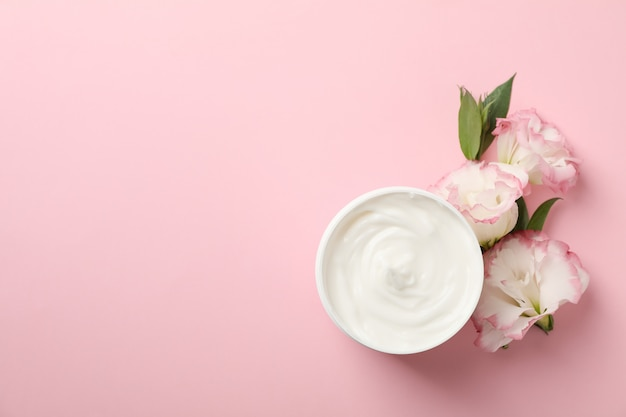 Cream and beautiful flowers on pink background, space for text