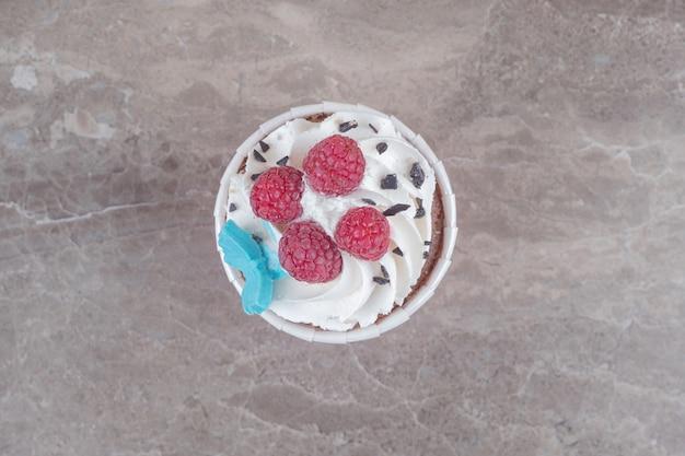 Un cupcake ricoperto di crema e frutti di bosco su marmo