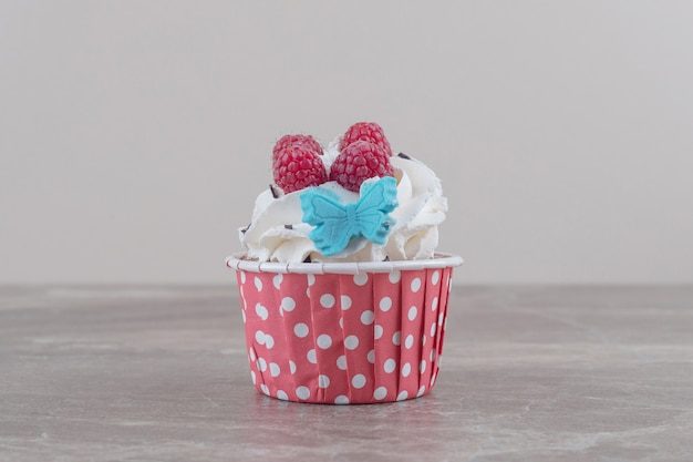 A cream and berry topped cupcake on marble