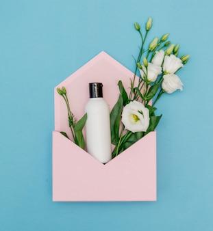 Кремовая бутылка с цветами в розовом конверте на синем фоне. вид сверху