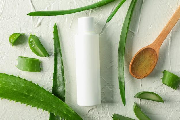 木のスプーン、アロエベラのスライス、白いテーブルの上の葉を持つクリームボトル