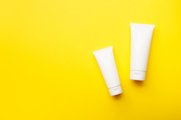 Cream bottles on bright yellow background, top view, copy space. cosmetics product and skin care concept. mock up.
