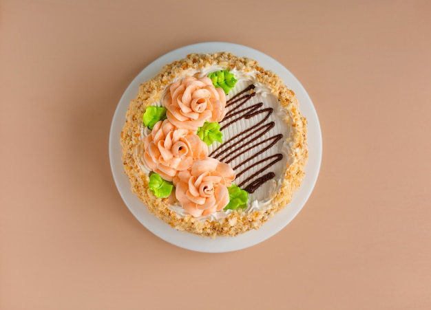 Cream cake of biscuits with creamy roses on the white plate over light
