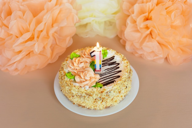Cream cake with creamy roses and flowers on the white plate