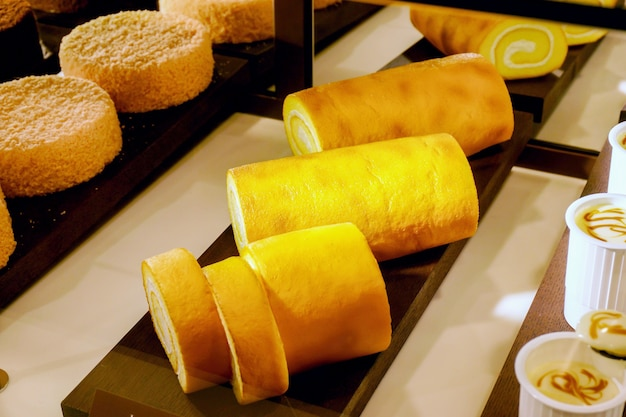 Cream cakes roll and on wood sheet display in showcase