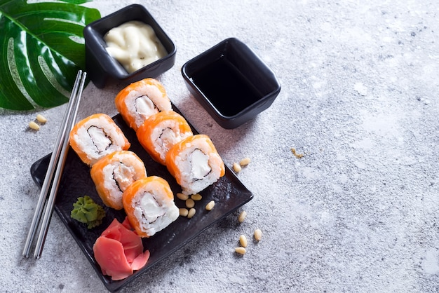 Cream cheese philadelphia roll classic on a stone black plate with chopsticks and sauce .