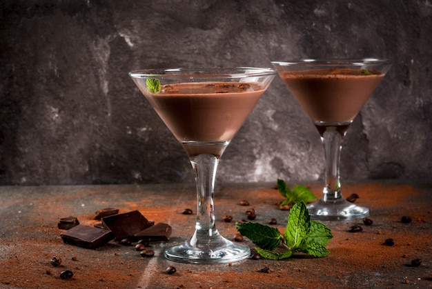 Cream coffee cocktail, chocolate martini with mint on black stone table,  copyspace